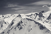 Winter mountains with snow cornice and sky with clouds