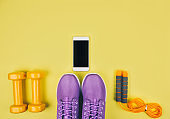 Flat lay shot of sneakers, dumbbells, jump rope or skipping rope and smartphone.