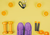 Flat lay shot of sneakers, dumbbells, jump rope
