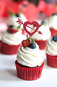 cupcakes with colored berries. Colorful cupcakes with buttercream and fresh berries