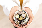 Young woman hands holding glass jar with multi currency coins inside