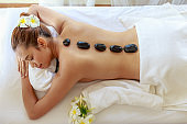 Top view of  young beautiful woman receiving hot black marble stone massage and relaxing in spa salon