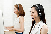 Asian woman telemarketing customer service agent team working in  call center