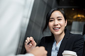 Beautiful smiling Asian woman leader meeting with client at office lounge