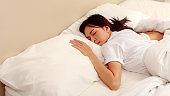 Young Asian woman sleeping in the bed, She is resting with eyes closed, people and morning concept, copy space