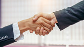 Two businessmen making handshake in the office, Business partnership meeting concept, Successful businessmen handshaking after good deal, Close up