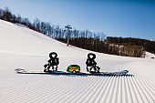Bottom view on empty ski slope and equipment for snowboarding