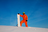 Snowboarder freerider with white snowboard standing on the top of the ski slope