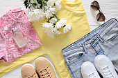 Womens fashion clothing, shoes and accessories (white and beige leather sneakers, blue jeans, yellow top (long sleeve t-shirt), pink blouse, perfume). Wish list or shopping overview, fashion concept. View from above, Flat lay. Trending. Spring season