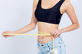 Closeup asian woman diet and slim with measuring waist for weight isolated on white background, girl have cellulite and calories loss with tape measure, health and wellness concept.