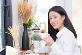 Beautiful  young asian woman drinking coffee and smile in the morning at cafe, girl sitting in coffee shop for breakfast and leisure during free time.