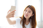 Beautiful portrait young asian woman taking a selfie with smart mobile phone on bedroom, girl is photographing with happy and smile with fun, lifestyle concept.