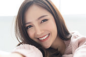 Closeup portrait of inspired caucasian Asian lady wearing knitted sweater pink cold smilling and taking selfie at her home.Concept woman lifestyle and winter. Model fashion shooting. Autumn, winter season.