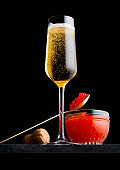 Elegant glass of yellow champagne with red caviar on golden spoon and glass container of caviar on marble board on black background.