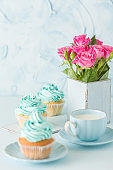 Blue pastel vertical banner with decorated cupcakes, cup of coffe with milk and bouquet of pink roses.