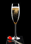 Elegant glass of yellow champagne with red caviar on golden spoon on marble board on black background.