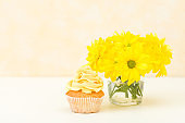 Cupcake with tender yellow cream decoration and bouquet of chrysanthemum in glass on yellow pastel background.