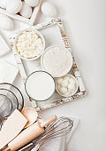 Fresh dairy products on white table background. Glass of milk, bowl of flour and cottage cheese and eggs. Box of baking utensils. whisk and spatula in vintage wooden box.Top view.