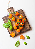 Organic Cherry Orange Rapture Tomatoes on the Vine with basil on chopping board on white kitchen background.