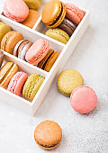 Dessert cake macaron or macaroon in white wooden box on stone kitchen table background . Top view.