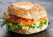Fresh healthy bagel sandwich with salmon, ricotta and lettuce in black plate on dark kitchen table background. Healthy diet food.