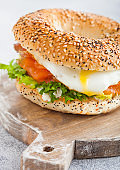 Fresh healthy bagel sandwich with salmon, ricotta and soft egg on vintage chopping board on white kitchen table background. Healthy diet food. Close up