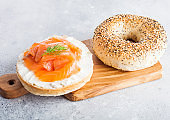 Fresh healthy bagel sandwich with salmon, ricotta and dill on vintage chopping board on light kitchen table background. Healthy diet food.