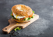 Fresh healthy bagel sandwich with salmon, ricotta and soft egg on vintage chopping board on stone kitchen table background. Healthy diet food. Space for text