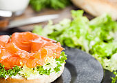 Fresh healthy bagel sandwich with salmon, ricotta and lettuce on black plate on black kitchen table background. Healthy diet food. Glass of milk and fresh vegetables