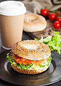 Fresh healthy bagel sandwich with salmon, ricotta and lettuce on black plate on black kitchen table background. Healthy diet food. Paper cup of coffee and fresh vegetables