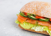 Fresh healthy salmon sandwich with lettuce and cucumber on white stone background. Breakfast snack. Diet food