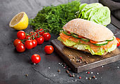 Fresh healthy salmon sandwich with lettuce and cucumber on vintage chopping board on black stone background. Breakfast snack. Fresh tomatoes, dill and lemon.