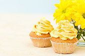 Cupcake with sweet yellow cream decoration and bouquet of yellow chrysanthemum in small glass