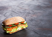 Fresh healthy salmon sandwich with lettuce and cucumber on black stone background. Breakfast snack. Space for text