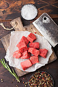 Raw lean diced casserole beef pork steak on chopping board with vintage meat hatchet on wooden background. Salt and pepper with fresh rosemary.