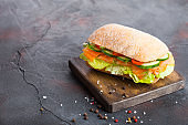 Fresh healthy salmon sandwich with lettuce and cucumber on vintage chopping board on black stone background. Breakfast snack. Diet food