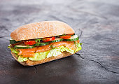 Fresh healthy salmon sandwich with lettuce and cucumber on black stone background. Breakfast snack. Diet food