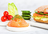 Fresh healthy salmon sandwich with lettuce and cucumber and tomatoes on marble board on white marble background. Breakfast snack.