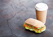 Fresh healthy salmon sandwich with lettuce and cucumber with paper cup of coffee on black stone background. Breakfast snack. Space for text