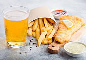 Traditional British Fish and Chips with tartar sauce abd glass of craft lager beer and tomato ketchup on chopping board on white stone table background.
