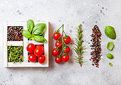 Organic Cherry Tomatoes with basil and pepper and rosemary in white wooden box on stone kitchen background. Cooking concept