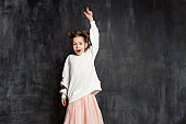Surprised little girl in an blank white sweatshirt and pink skirt shows an index finger up against a school chalkboard.
