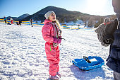 Cheerful Daughter Excited for Tobogganing