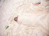Young Carefree Girl Burried Under Sand on a Beach