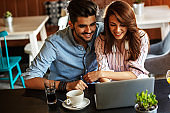 Young couple sitting at the internet cafe and relaxing on coffee break.