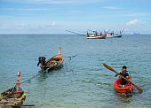 Man Kayaking from Longtail Boats and Commercial Fishing boats