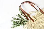 Styled stock photo. Feminine still life composition with straw French basket bag with long leather handles and eucalyptus branches on white backgouns. Flat lay, top view.