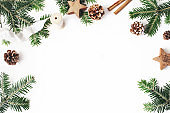 Christmas festive styled stock composition. Decorative floral frame. Fir tree branches border. Pine cones, wooden stars, cinnamon and ribbon on white wooden background. Flat lay, top view. Copy space.