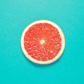 Grapefruit slice on pastel blue background. Minimal summer concept. Flat lay.