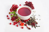 Parts of a pomegranate with pomegranate seeds and leaves, flowers, dry tea of carcade and full cup of tea isolated on white background